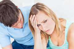 Handsome man apologizing after an argument. With his girlfriend sitting in the living-room Stock Photography