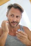 Handsome man applying anti-aging cream on Royalty Free Stock Image