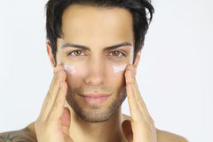 Handsome man applying cream on his face Stock Photos