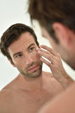 Handsome man applying lotion on face Royalty Free Stock Image