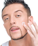 Handsome man applying male creme on face. Close up portrait of young handsome man applying male cosmetic creme on face Stock Photo