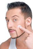 Handsome man applying male creme on face Stock Photography