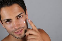 Handsome man applying a moisturizing cream on his face. Handsome man applying a moisturizing cream on a gray background Royalty Free Stock Image
