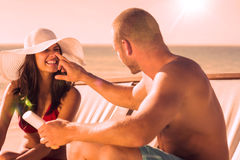 Handsome man applying sun cream on his girlfriends nose Stock Image