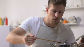 Handsome man in apron cooking, stirring ingredients in pan and trying meal. Stock footage stock footage