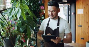 Handsome man in apron enjoying flowers in florist`s shop using tablet working. Touching screen standing alone in workplace. People, job and technology concept stock video footage