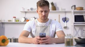 Handsome man in apron looking for culinary recipe in internet, kitchen novice. Stock footage stock footage
