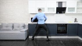 Handsome man in an apron and tie in the kitchen wipes a table and dances. stock footage