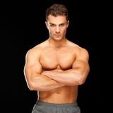 Handsome man with arms crossed looking his left on black stock photos