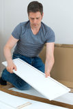 Handsome man assembling furniture. Royalty Free Stock Image