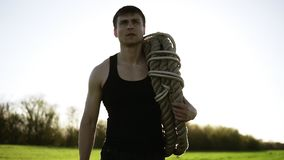 A handsome man, an athlete carries coiled battle ropes on his shoulder after training in the park. Crossfit. Sunny. Background stock footage