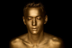 A handsome man of athletic build, completely covered in gold paint. Studio photos Stock Photos
