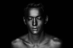 A handsome man of athletic build, completely covered in gold paint. Studio photos. Black and white Royalty Free Stock Photography