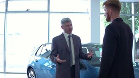 Handsome man at auto showroom talking with vehicle dealer. stock footage
