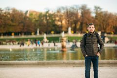 Handsome man with backpack posing for photographer in park royalty free stock image