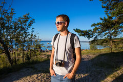 Handsome man with backpack and retro camera on the beach Royalty Free Stock Image