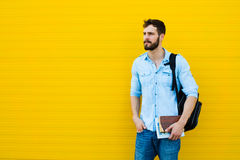 Handsome man with backpack on yellow Stock Photo