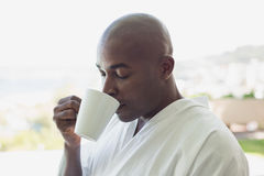Handsome man in bathrobe drinking coffee outside Stock Image