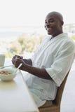 Handsome man in bathrobe having breakfast outside Stock Photos