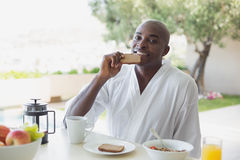 Handsome man in bathrobe having breakfast outside Royalty Free Stock Photos