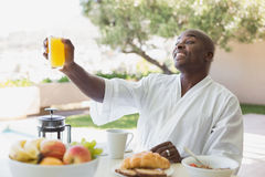 Handsome man in bathrobe having breakfast outside Royalty Free Stock Photography
