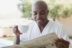 Handsome man in bathrobe having coffee outside Royalty Free Stock Photography