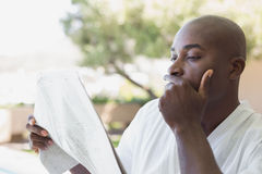 Handsome man in bathrobe reading newspaper outside Royalty Free Stock Image