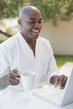 Handsome man in bathrobe using laptop at breakfast outside Royalty Free Stock Photography