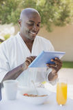 Handsome man in bathrobe using tablet at breakfast outside Royalty Free Stock Image