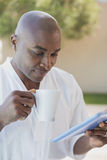 Handsome man in bathrobe using tablet at breakfast outside Stock Photo