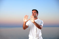 Handsome man on the beach meditating Royalty Free Stock Images