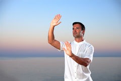 Handsome man on the beach meditating Stock Photos