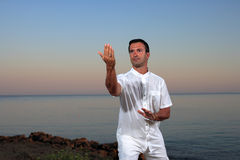 Handsome man on the beach meditating Stock Photography