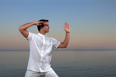 Handsome man on the beach meditating Stock Photo