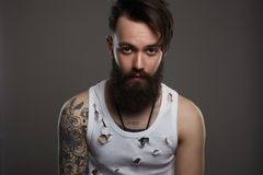 Man with beard. Boy with stylish haircut and tattoo stock image