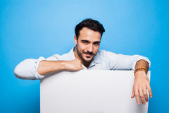 Handsome man with beard casual dressed holding a blank panel on Stock Images