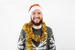 A handsome man with a beard, in a Christmas sweater, wearing a Santa Claus hat royalty free stock images