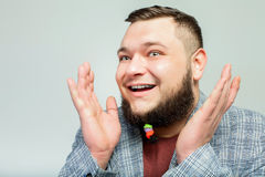 Handsome man with beard. Close up portrait of handsome happy fat man with hair clips on long beard over gray background. Concept of comic, hairdo, hair style Royalty Free Stock Photos