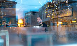 Handsome man with beard in coffee shop with lights reflecting stock photos