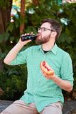 Goodly boy with a glasess tasting delicious food in the park. Nature background. Royalty Free Stock Photos