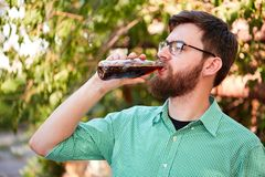 Goodly boy with a glasess tasting delicious food in the park. Nature background. Stock Image
