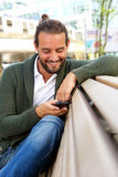 Handsome man with beard holding cellphone sitting on bench Stock Photos