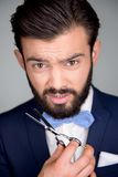 Handsome man with beard holding scissors Stock Images