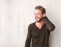 Handsome man with beard laughing with hand in hair Stock Images