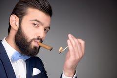 Handsome man with beard lighting cigar Stock Photo
