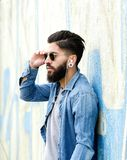 Handsome man with beard listening to music with earphones Stock Photos