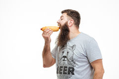 Handsome man with beard standing and eating hot dog Stock Photo
