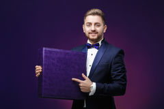 Handsome man with beard in tuxedo holds large box and smiling on Stock Photography
