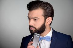 Handsome man with beard using electric shaver Royalty Free Stock Image