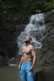 Handsome man with beard wearing blue shorts standing and looking up near waterfall. Male tourist enjoying by a water fall in forest Stock Photography